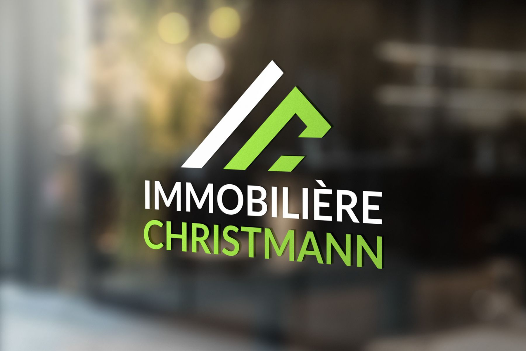 "Sticker of the ""Immobilière Christmann"" logo in their shop window."